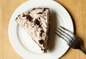 Photo of a slice of grasshopper pie shot from above on a white plate with a fork on the side.