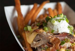 Photo of loaded sweet potato fries in a paper basket. Fries have pork, bacon, cheese, sour cream, chives.