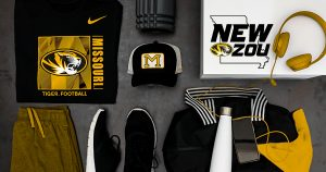 Photo showing a top-down look at black and gold apparel products with Mizzou marks. T-shirt, hat, pants, shoes, headphones.