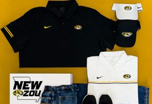 Photo of Mizzou-branded Nike apparel including polos, hats, visors and shirts in white and black on a gold background.