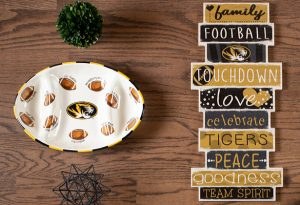 Photo of a ceramic dish with University of Missouri Athletic tiger head and footballs next to a home decor sign.