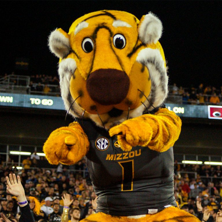 Photo of Missouri Tigers mascot Truman the Tiger in the football stadium pointing at the camera with crowd of fans in the backgrounds.