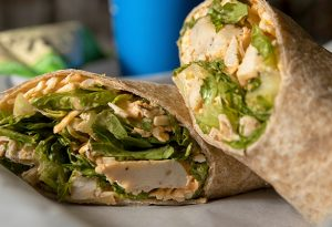 Photo of a buffalo chicken wrap with chicken, lettuce and cheese.