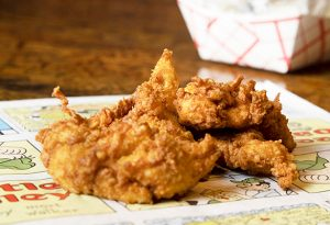 Photo of crispy chicken tenders on a piece of parchment paper.