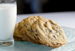 Photo of five chocolate cookies stacked on a glass plate next to a glass of white milk.