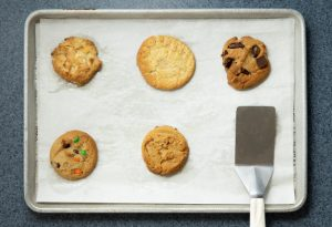 Photo of a variety of cookies on a sheet pan next to a spatula.