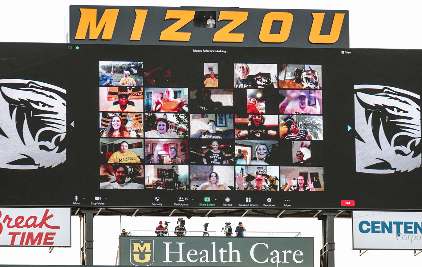 Photo of the digital display board at Faurot field showing a Zoom screen of Virtual Fans watching the game.