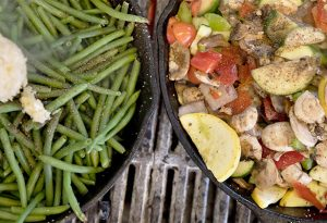 Photo of two cast iron skillets on a grill filled with veggies. Left skillet is filled with green beans, the right skillet is a mix of tomatoes, peppers, onions, squash and mushrooms.