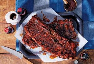 Photo of a rack of ribs with sauce on a wood table and a blue checkered cloth. Bottles of coke, a container of sauce, a roll of napkins and a knife surround the platter of ribs.