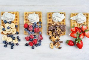 Photo of waffles with whipped cream and assorted berries and toppings such as bananas, blueberries, raspberries, walnuts, chocolate, and strawberries