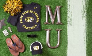 """Photo of products on a fake green grass background. Mizzou Nike t-shirt with state outline, Athletic tiger head and text """"Pride. Passion. Purpose. Football."""""""