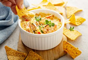 Photo of a seafood cheese dip with tortilla chips.
