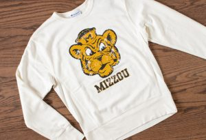 Photo of a white sweatshirt with gold and black vintage Mizzou Sailor Tiger mark.