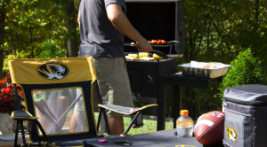 Photo of man grilling in background with a Mizzou branded lawn chair and cooler in the foreground.