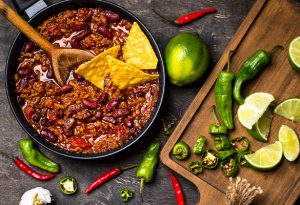Photo of a pot of chili surrounded by peppers and a cutting board.