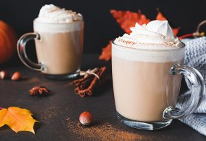 Photo of two clear glass cups of hot chocolate with whipped cream surrounded by hazelnuts, fall leaves and cinnamon sticks.