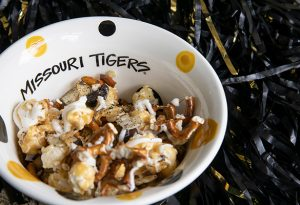 """Photo of Mizzou Munch in a """"Missouri Tigers"""" bowl next to a black and gold pom pom."""