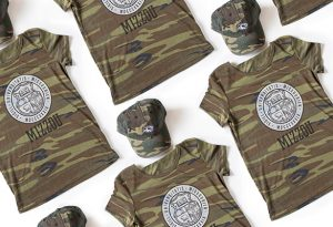 "Photo of camo t-shirt and hat with ""Mizzou"" and spirit tiger head and UM seal."