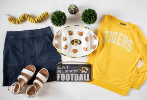 "Outfit of the Week showing a photo flat lay of a tiger tail, denim skirt, white platform sandals, ceramic food tray, ""Eat Sleep Football"" wall sign and a gold ""Tigers"" sweater."