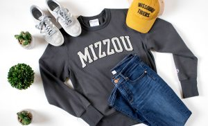 "Photo of a gray ""Mizzou"" sweatshirt and gold ""Missouri Tigers"" hat."