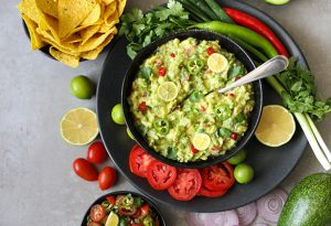 Photo of guacamole in a bowl with spoon next to tortilla chips, limes, tomatoes, and peppers.