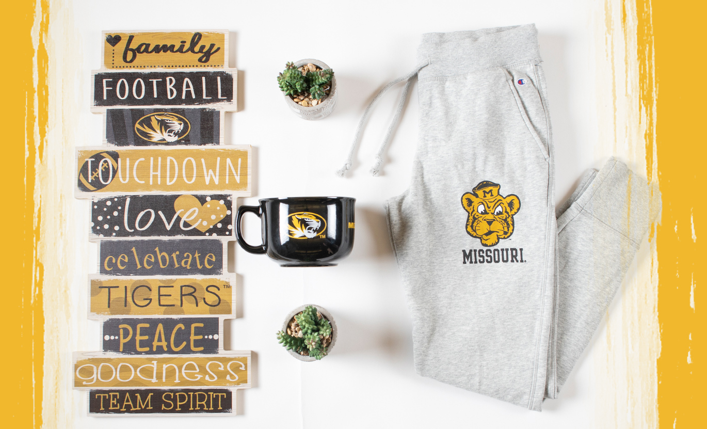 Photo of sweat pants, wall decoration and large mug with University of Missouri logos.